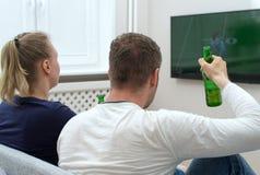 Pares que olham o futebol americano imagens de stock