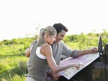 Pares que olham o mapa em Jeep Bonnet At Landscape imagem de stock