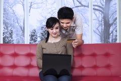 Pares que pagan en línea en casa Imagen de archivo libre de regalías