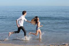 Pares que perseguem e que correm na praia Fotos de Stock Royalty Free