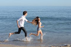 Pares que persiguen y que corren en la playa Fotos de archivo libres de regalías