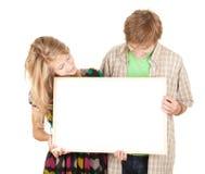 Pares que prendem o quadro de avisos em branco, poster Imagem de Stock