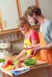 Pares que preparan la ensalada de la comida de las verduras frescas Fotografía de archivo libre de regalías
