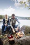 Pares que preparan la hoguera durante acampar de la orilla del lago Fotos de archivo