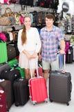 Pares que presentan cerca de las maletas en tienda Fotos de archivo libres de regalías
