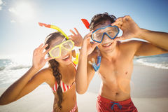 Pares que presentan con la máscara del salto en la playa imágenes de archivo libres de regalías