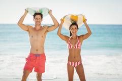 Pares que presentan con la tabla hawaiana en la playa Fotografía de archivo libre de regalías