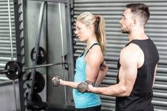 Pares que presentan con pesas de gimnasia Foto de archivo libre de regalías