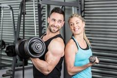 Pares que presentan con pesas de gimnasia Imagen de archivo