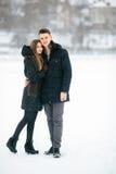 Pares que presentan en un parque nevoso Fotografía de archivo libre de regalías