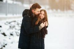 Pares que presentan en un parque nevoso Fotos de archivo libres de regalías