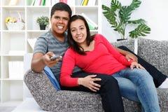 Pares que prestam atenção à tevê em sua sala de visitas Foto de Stock Royalty Free