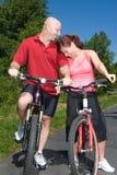 Pares que ríen mientras que en las bicicletas - vertical fotos de archivo libres de regalías