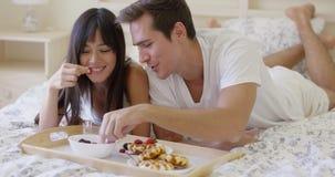 Pares que ríen nerviosamente que desayunan en cama almacen de video