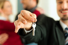 Pares que reciben claves de corredor de propiedades inmobiliarias Imagen de archivo libre de regalías