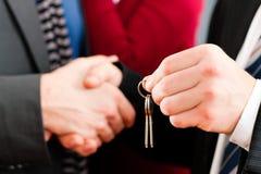 Pares que reciben claves de corredor de propiedades inmobiliarias Imagenes de archivo