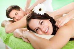 Pares que reciben masaje del hombro en el balneario Imagen de archivo libre de regalías