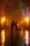 Pares que recorren en el callejón en luces de la noche Foto de archivo libre de regalías