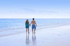 Pares que recorren en la playa Foto de archivo libre de regalías