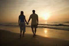 Pares que recorren en la playa en la puesta del sol. Foto de archivo