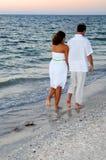 Pares que recorren en la playa en la puesta del sol fotografía de archivo