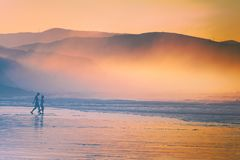 Pares que recorren en la playa en la puesta del sol Foto de archivo