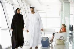 Pares que recorren a través de salón de la salida del aeropuerto Imagen de archivo libre de regalías