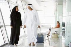 Pares que recorren a través de salón de la salida del aeropuerto Fotografía de archivo libre de regalías