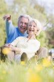 Pares que relaxam ao ar livre apontar e sorrir imagens de stock royalty free