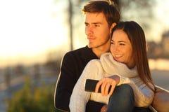 Pares que relaxam e que abraçam olhando o por do sol imagens de stock royalty free