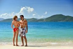 Pares que relaxam em uma praia tropical. Imagem de Stock