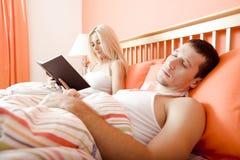 Pares que relaxam na cama foto de stock royalty free