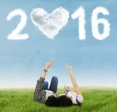 Pares que relaxam na grama sob os números 2016 Foto de Stock Royalty Free