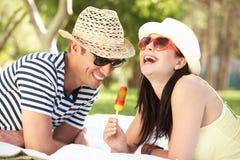 Pares que relaxam no jardim que come o Lolly de gelo imagens de stock royalty free