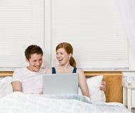Pares que ríen y que usan la computadora portátil en cama Imágenes de archivo libres de regalías