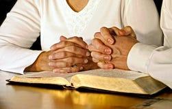 Pares que ruegan con la Sagrada Biblia foto de archivo