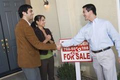 Pares que sacuden las manos con el agente de la propiedad inmobiliaria Imágenes de archivo libres de regalías