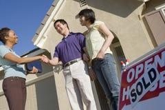 Pares que sacuden las manos con el agente de la propiedad inmobiliaria de sexo femenino foto de archivo libre de regalías