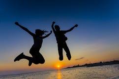 Pares que saltam no por do sol Fotografia de Stock Royalty Free