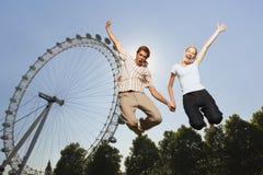 Pares que saltan en aire contra el ojo de Londres en el parque Fotografía de archivo libre de regalías