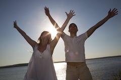 Pares que saltan para la alegría en la playa imagen de archivo libre de regalías