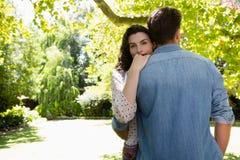 Pares que se abrazan en jardín Foto de archivo libre de regalías