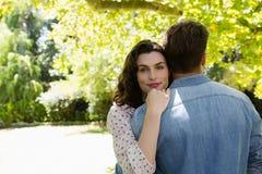 Pares que se abrazan en jardín Foto de archivo
