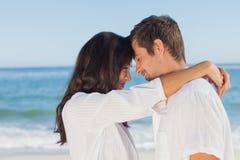 Pares que se abrazan en la playa Fotos de archivo libres de regalías