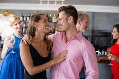 Pares que se abrazan en restaurante Fotografía de archivo libre de regalías