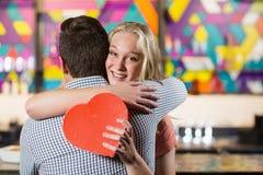 Pares que se abrazan mientras que sostiene el regalo Imagenes de archivo