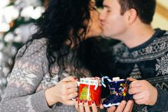 Pares que se besan con las tazas de la melcocha del chocolate caliente de la Navidad foto de archivo libre de regalías