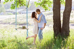 Pares que se besan de los jóvenes debajo del árbol grande con el oscilación Fotos de archivo libres de regalías
