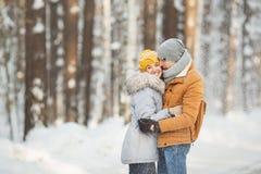 Pares que se besan de los jóvenes en un bosque del invierno Fotografía de archivo libre de regalías