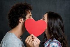 Pares que se besan detrás del corazón de papel Fotografía de archivo libre de regalías
